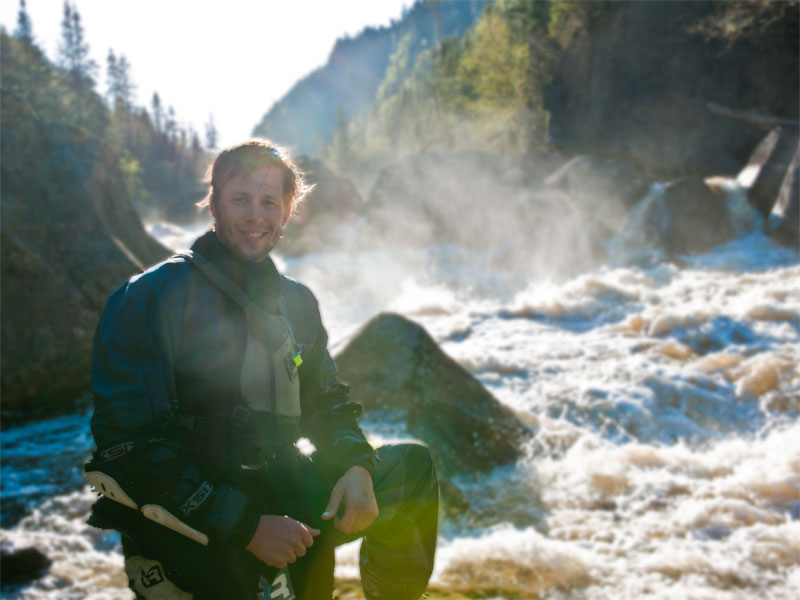 Chris Schwer posing in front of the second largest rapid on the Jaques-Cartier Northwest near Quebec City, Canada.
